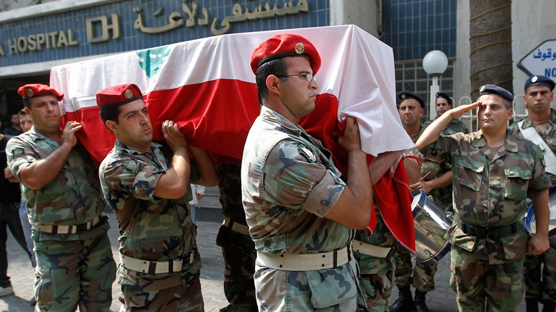 Lebanese army soldiers from the military police unit carry the coffin of Sgt. Robert Ashi, who was killed Tuesday during a clash with the Israeli army, during his funeral procession outside a hospital, in the southern port city of Sidon, Lebanon, Wednesday, Aug. 4, 2010. (AP / Hussein Malla)