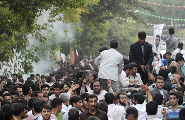 Smoke rises next to a vehicle transporting Iranian President Mahmoud Ahmadinejad, centre, as he arrives in the city of Hamedan, 340 kilometres southwest of the capital Tehran, Iran, Wednesday, Aug. 4, 2010. (ISNA / Saman Aghvami)