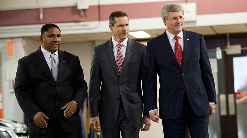 Prime Minister Stephen Harper, right, walks with President of General Motors Canada Kevin Williams, left and Ontario Premier Dalton McGuinty, centre, at the General Motors Plant in Oshawa, Ontario on Tuesday July 24, 2012. (Aaron Vincent Elkaim / THE CANADIAN PRESS)