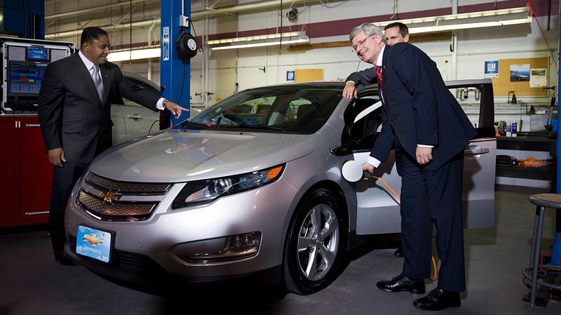 Prime Minister Stephen Harper plugs in a GM Volt electric car for a photo opportunity with Kevin Williams, the president of General Motors Canada , left, and Ontario Premier Dalton McGuinty, right, at the General Motors Plant in Oshawa, Ont. on Tuesday, July 24, 2012. (Aaron Vincent Elkaim / THE CANADIAN PRESS)