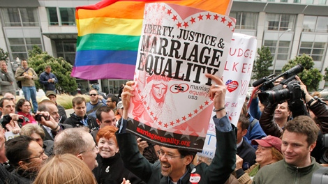 Stuart Gaffney, center, holds up a sign while celebrating the decision in the United States District Court proceedings challenging Proposition 8 outside of the Phillip Burton Federal Building in San Francisco, Wednesday, Aug. 4, 2010. (AP Photo/Eric Risberg)