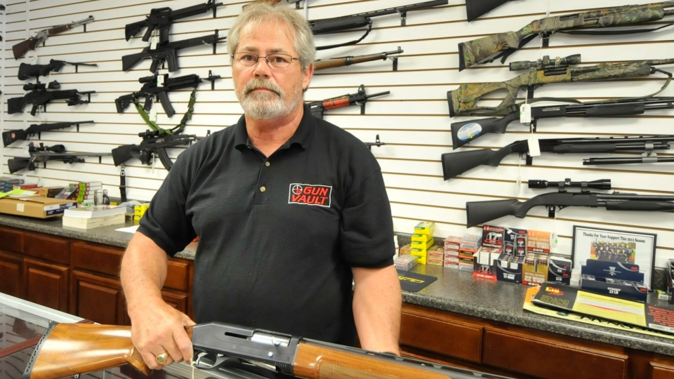 Randy Hodges holds a firearm at the Gun Vault in High Point, N.C. Monday, July 23, 2012. (AP / The Enterprise, Sonny Hedgecock)