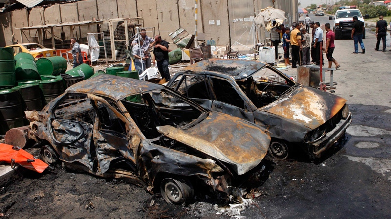 People inspect the aftermath of a car bomb attack in Baghdad's Shiite enclave of Sadr City, Iraq, Monday, July 23, 2012.  (AP / Karim Kadim)