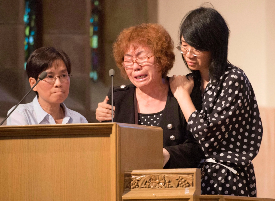 The mother of Lin Jun, Zhi Gui Du cries uncontrollably as she is comforted by a friend (right) as she speaks about her son during a public memorial for Lin in Montreal Saturday, July 21, 2012. A translator looks (left) on. (Peter McCabe / THE CANADIAN PRESS)