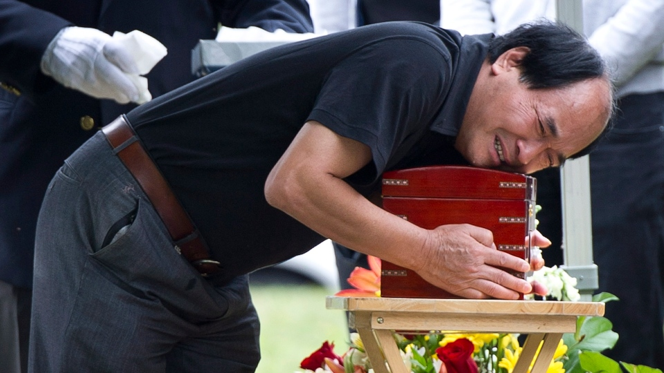 Daran Lin breaks down as he hugs the urn bearing the remains of his son, murder and dismemberment victim Lin Jun, during funeral services Thursday,  July 26, 2012 in Montreal. (Paul Chiasson / THE CANADIAN PRESS)