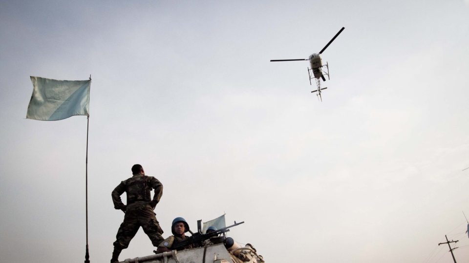 A United Nations helicopter circles overhead as U.N. peacekeepers from Uruguay patrol in a show of force to reassure the local population, in Goma, eastern Congo July 13, 2012.  (AP Photo/Marc Hofer)
