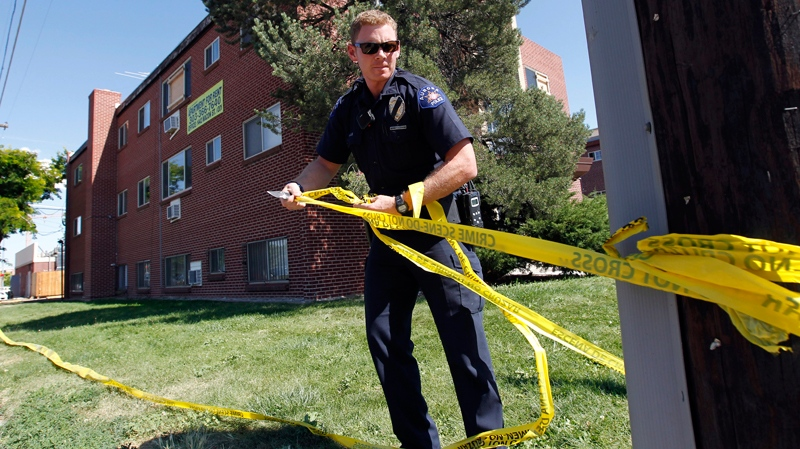 An Aurora police officer removes the crime scene tape from around the apartment where accused killer James Holmes lived in Aurora, Colo., on Thursday, July 26, 2012. (AP / Alex Brandon)