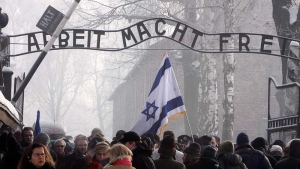 """In this Jan. 27, 2010 file photo, visitors from around the world pass under the infamous Arbeit Macht Frei """"Work Sets You Free"""" sign over the main gate at the former Nazi death camp Auschwitz in Poland. (AP Photo/Czarek Sokolowski,File)"""