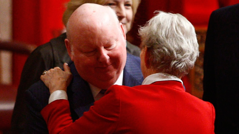 Sen. Mike Duffy is embraced by Sen. Joyce Fairbairn prior to the Speech from the Throne on Parliament Hill in 2009. (Tom Hanson / THE CANADIAN PRESS)