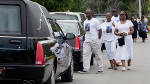 Mourners gather outside of Highland Funeral Home wearing shirts with a photo of shooting victim to Shyanne Charles in Toronto on Saturday, July 28, 2012. (Michelle Siu / THE CANADIAN PRESS)