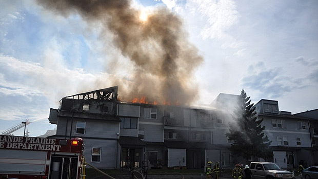 Officials say a barbecue was the cause of a fire that tore through a Grande Prairie condominium and forced residents out of their homes on Friday. Photo: William Vavrek.