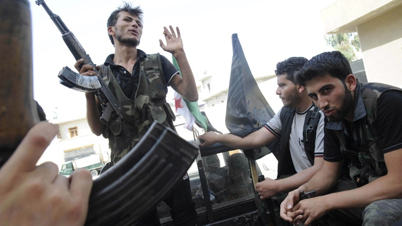 Syrian rebels sit in a pick up truck in Aleppo, Syria, Saturday, July 28, 2012. (AP Photo/Alberto Prieto)