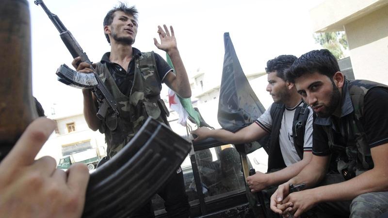 Syrian rebels sit in a pick up truck in Aleppo, Syria, Saturday, July 28, 2012. (AP Photo/Alberto Prieto)