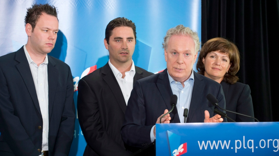 Quebec Premier Jean Charest speaks during a press conference in Montreal on Sunday, July 29, 2012. Charest has announced candidates Pascal Beaupre (left) in Joliette, Jean Francois Gosselin (centre) in La Peltrie, and Linda Lapointe (right) in Groulx. (Peter McCabe / The Canadian Press)