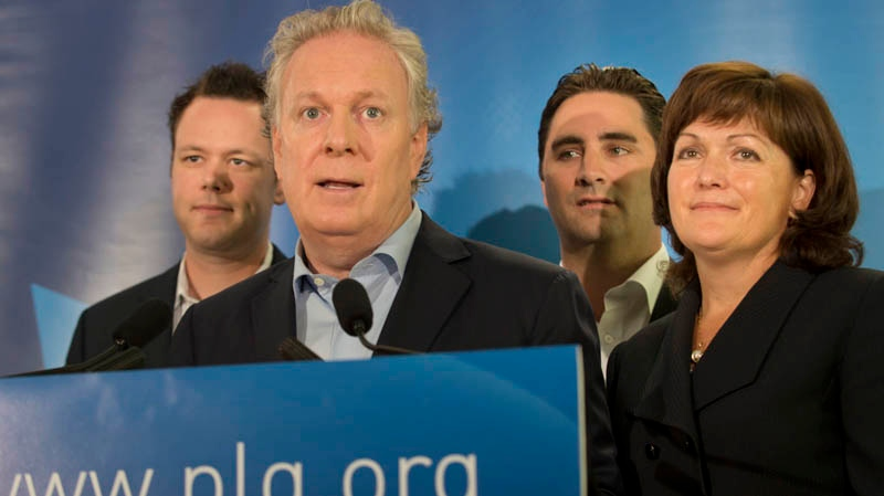 Quebec Premier Jean Charest speaks during a press conference in Montreal on Sunday, July 29, 2012. Charest has announced candidates Pascal Beaupre (left) in Joliette, Jean Francois Gosselin (centre) in La Peltrie, and Linda Lapointe (right) in Groulx. THE CANADIAN PRESS/Peter McCabe