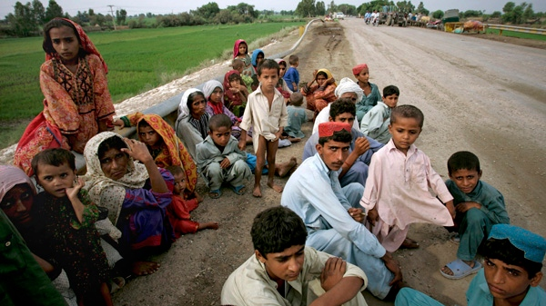 Pakistani families wait for transport after they were rescued from a heavy flooded area of Toree Band near Sukkur, in Pakistan's Sindh province, Sunday, Aug. 8, 2010. (AP / Shakil Adil)