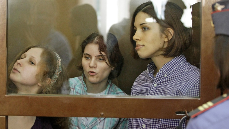 From left, Yekaterina Samutsevich, Maria Alekhina, and Nadezhda Tolokonnikova, members of feminist punk group Pussy Riot, sit behind bars at a court room in Moscow, Russia, Monday, July 30, 2012.