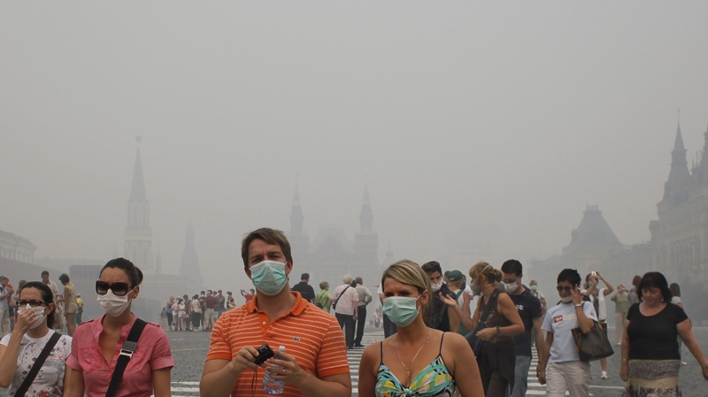 Tourists with face masks walk along Red Square in a thick blanket of smog, in Moscow, Russia, Monday, Aug. 9, 2010. (AP / Alexander Zemlianichenko)
