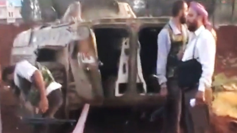 This image made from amateur video released by the Ugarit News and accessed Monday, July 30, 2012, purports to show Free Syrian Army soldiers standing near a destroyed vehicle in 16 kilometers (10 miles), from Aleppo, Syria. (AP / Ugarit News via AP video)