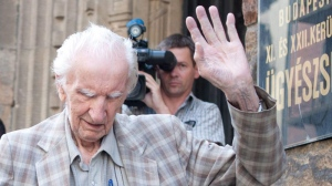 Alleged Hungarian war criminal Laszlo Csatary, right, waves and is helped by a relative as he leaves the Budapest Prosecutor's Office after he was questioned by detectives on charges of war crimes during WWII and prosecutors ordered his house arrest in Budapest, Hungary, Wednesday, July 18, 2012.