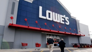 In a Nov. 14, 2011, file photo, customers walk into a Lowe's store in Saugus, Mass. (AP Photo/Michael Dwyer/file)