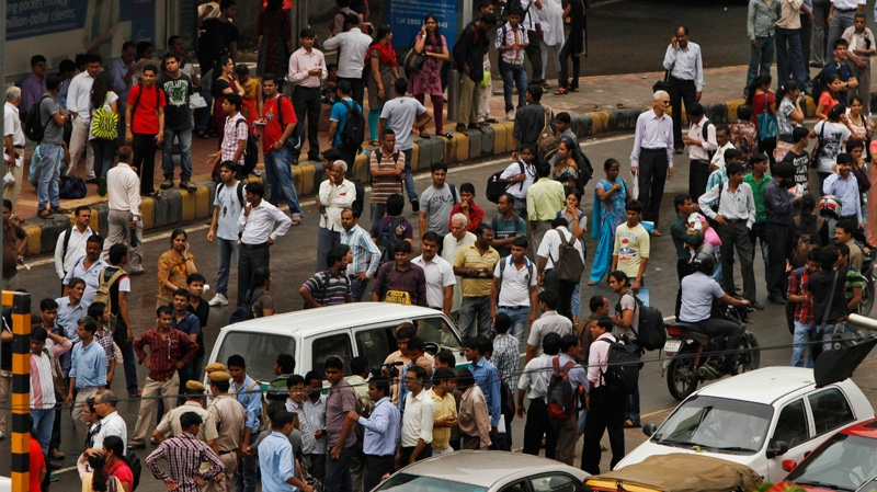 Commuters crowd a busy road outside a Metro station after Delhi Metro rail services were disrupted following a power outage in New Delhi, India, Tuesday, July 31, 2012. (AP Photo/ Rajesh Kumar Singh)