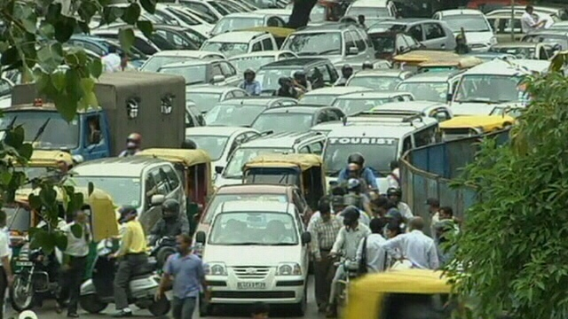 Commuters crowd a busy road following a power outage in New Delhi, India, Tuesday, July 31, 2012.