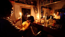 An Indian barber holding a candle