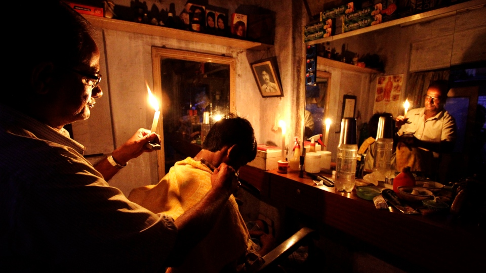 An Indian barber holding a candle, has a haircut for a customer at his shop in Kolkata, India, Tuesday, July 31, 2012. (AP / Bikas Das)