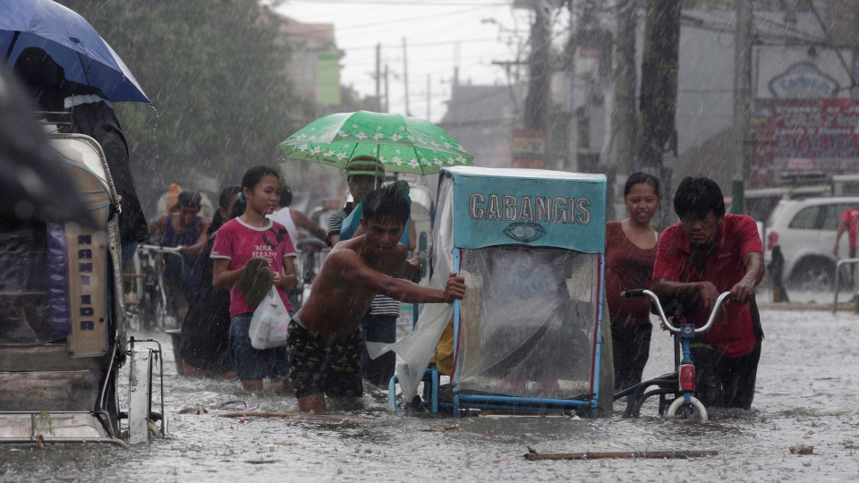 Drivers push their pedicab during a sudden downpour along floodwaters at Navotas city, north of Manila, Philippines, Wednesday, Aug. 1, 2012. (AP / Aaron Favila)