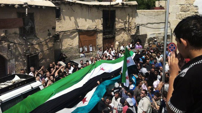 This citizen journalism image purports to show Syrians holding a large Syrian revolutionary flag during the funeral procession of Mohammed al-Naan in Damascus, Syria, taken on Wednesday, Aug. 1, 2012. (AP / Shaam News Network, SNN)
