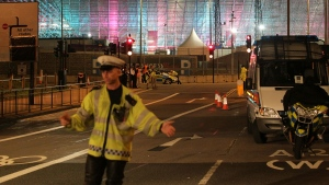 A police officer stands at the scene where the driver of an official Olympic bus carrying journalists has been arrested after a bicyclist was hit and killed, near the Olympic Park in Stratford, London, Wednesday, Aug. 1, 2012. (AP / Yui Mok, PA)