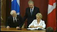 Lieutenant Governor Pierre Duchesne and Premier Jean Charest witness Monique Gagnon-Tremblay affirming her new job as Minister of Intergovernmental Relations (August 11, 2010)