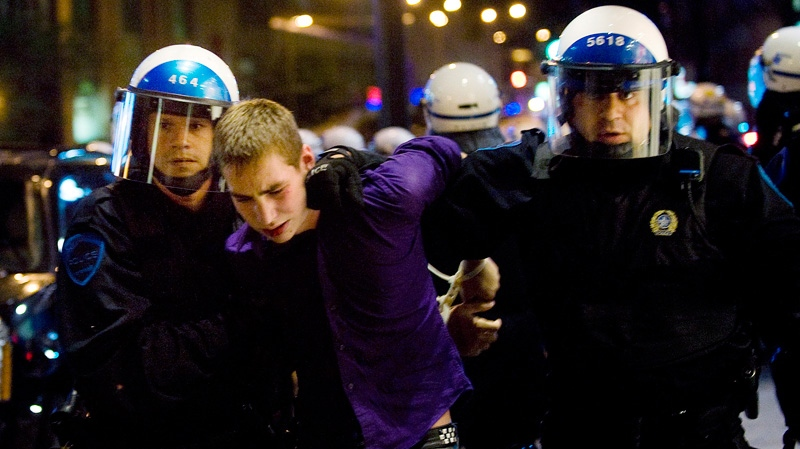 Police officers detain a man during a demonstration opposing Quebec student tuition fee hikes in Montreal on day one of the provincial election Wednesday, August 1, 2012. (Graham Hughes / THE CANADIAN PRESS)