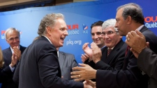 Quebec Liberal Leader Jean Charest, left, greets candidate Sam Hamad, right, as Taschereau candidate