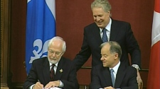 Lieutenant Governor Pierre Duchesne signs the book confirming Raymond Bachand's new role as Finance and Revenue Minister, as Premier Jean Charest looks on. (August 11, 2010)