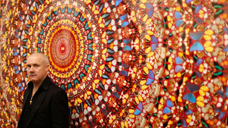 British artist Damien Hirst stands beside the 2006 piece