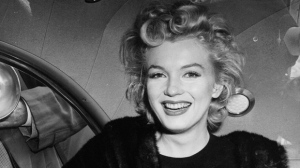 In this file photo, actress Marilyn Monroe smiles in a car after arriving from an all-night plane flight from Hollywood to Idlewild Airport in New York. (AP, File)