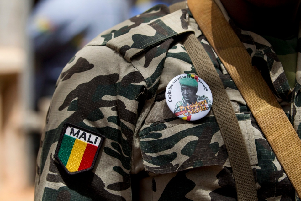 In this April 1, 2012 file photo, a soldier wears a button bearing the image of coup leader Capt. Amadou Haya Sanogo with the words 'President, CNRDRE,' the French acronym of the ruling junta, as he stands guard at junta headquarters in Kati, outside Bamako, Mali. (AP / Rebecca Blackwell)