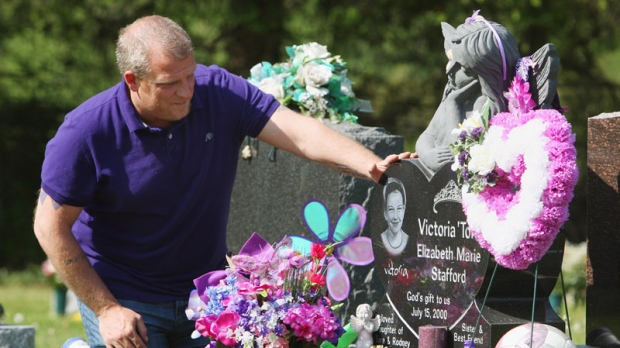 Rodney Stafford, father of slain Victoria Stafford, puts his hand on Victoria's grave marker, after the sentencing of Michael Rafferty who was found guilty on all three charges at the murder trial in London, Ontario, Tuesday, May 15, 2012. (Dave Chidley / THE CANADIAN PRESS)