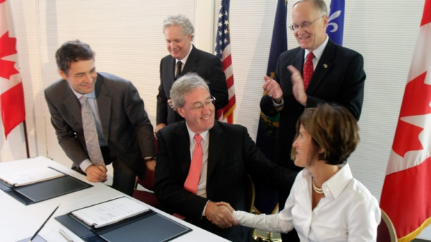 Bob Young of Central Vermont Public Service, center, shakes hands with Mary Powell of Green Mountain Power, right, as Christian Brosseau of Hydro Quebec, left, looks on following the signing of a power deal in Essex, Vt., Thursday, Aug. 12, 2010. (AP / Toby Talbot)