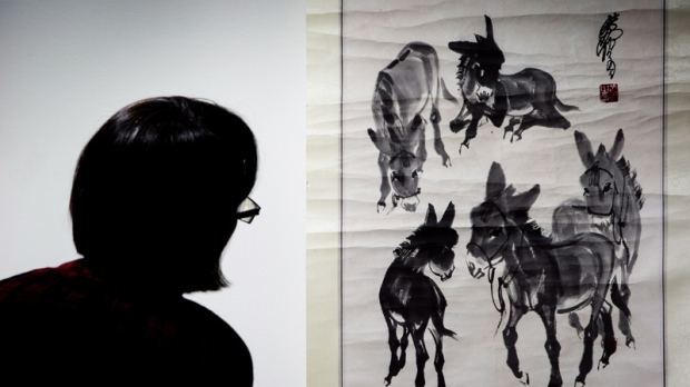 A woman looks at a fake painting of Chinese modern-artist Zhou Huang's 'Five Spirited Horses'.