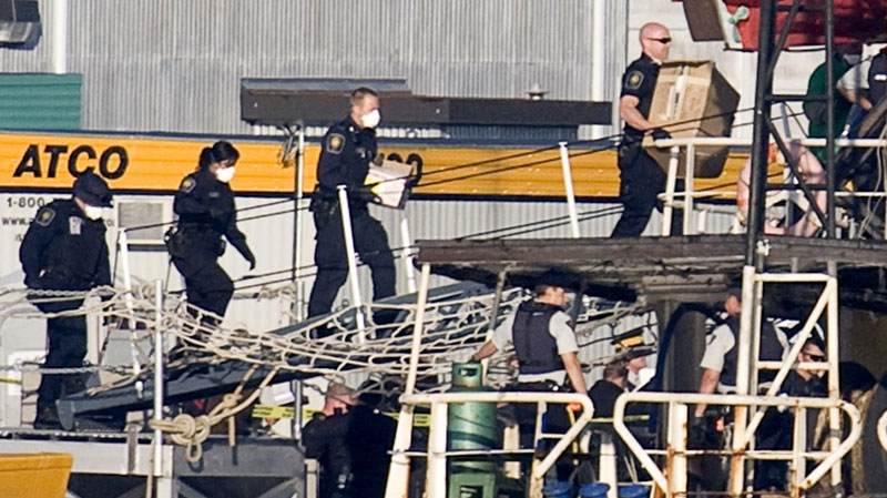 Members of the RCMP are seen wearing surgical masks as they board the MV Sun Sea after it was escorted into CFB Esquimalt in Colwood, B.C.,Friday, Aug. 13, 2010. (Jonathan Hayward / THE CANADIAN PRESS)