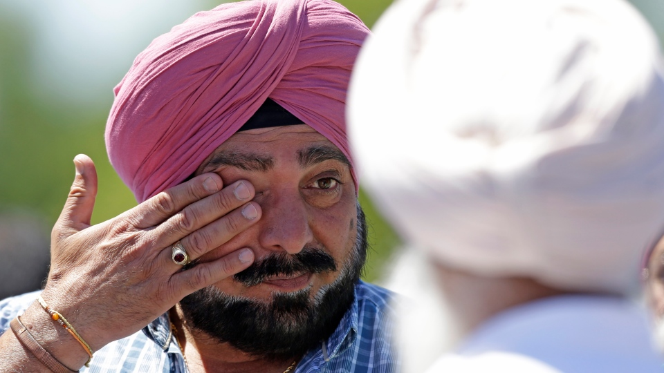 A man wipes away tears outside the Sikh Temple in Oak Creek, Wis. where a shooting took place on Sunday, Aug 5, 2012. (AP / Jeffrey Phelps)