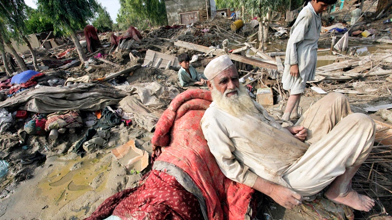 Pakistani flood affected villagers sit in the rubble of their houses, in Aza Kheil near Peshawar, Pakistan on Friday, Aug. 13, 2010. (AP / Mohammad Sajjad)