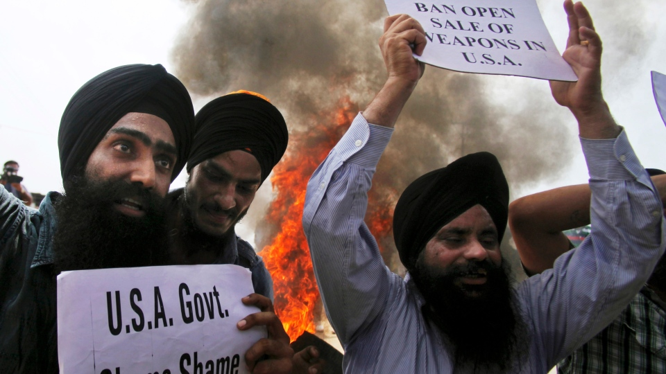 Sikh men hold placards and shout slogans during a protest against the deadly shooting attack at a Sikh temple in Wisconsin, in Jammu, Monday, Aug. 6, 2012. (AP / Channi Anand)