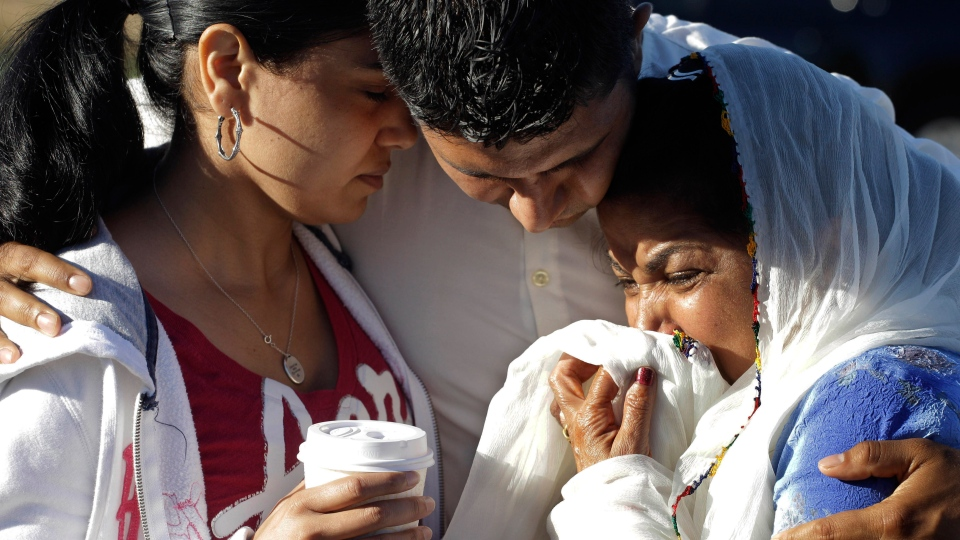 Amardeep Kaleka, son of the president of the Sikh Temple of Wisconsin, centre, comforts members of the temple, in Oak Creek, Wis., Monday, Aug. 6, 2012. (AP / M. Spencer Green)
