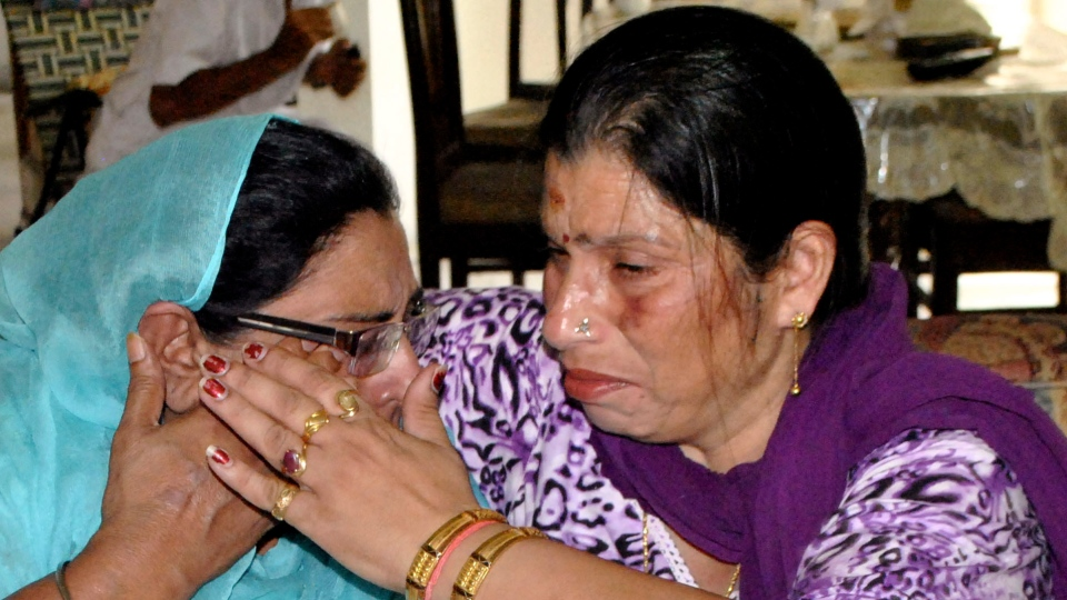 Harinder Kaur Rakhra, left, sister of Satwant Singh Kaleka who was killed in the shooting attack at a Sikh temple in the U.S. state of Wisconsin, is consoled by Seema Sharma, a local politician in Patiala, India, Monday, Aug. 6, 2012. (AP / Rajesh Sachar)