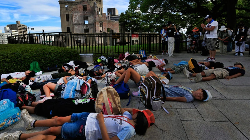 Students lie on the ground pretending to die in front of the Atomic Bomb Dome to mark the 67th anniversary of the atomic bombing in Hiroshima, Japan, Monday, Aug. 6, 2012. (AP / Vincent Yu)