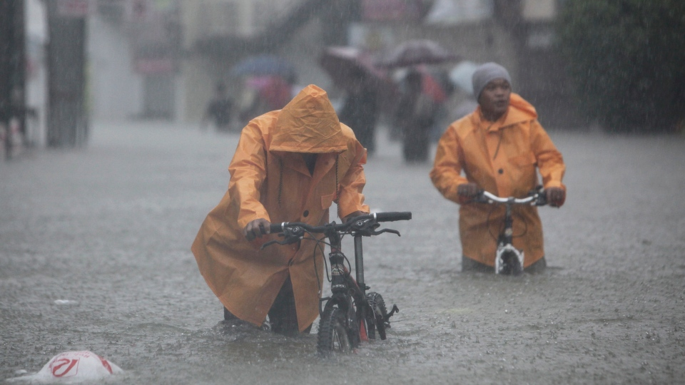 Two men push their bikes along a flooded area in Rizal, east of Manila, Philippines on Tuesday Aug. 7, 2012. (AP / John Javellana)